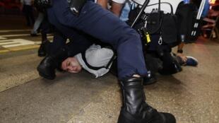 香港金钟地区一名占中示威者被警察按倒在地,2014年11月26日。