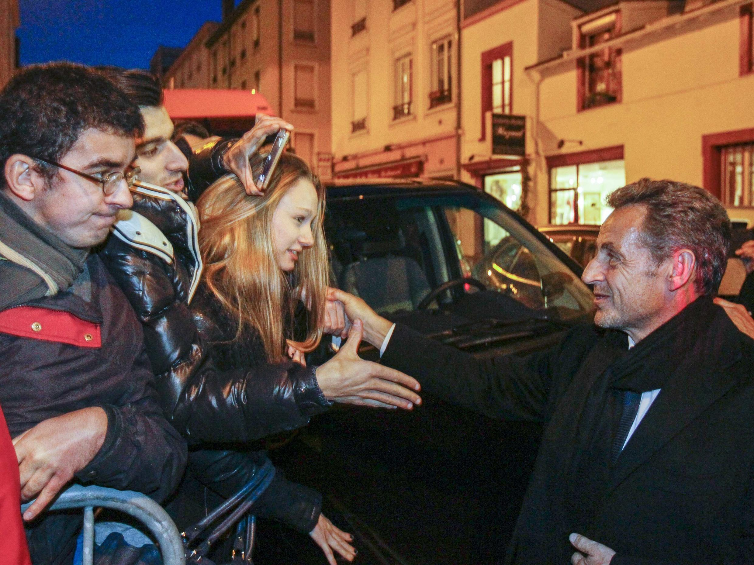 Nicolas Sarkozy shakes hands with supporters at his wife's concert in Lyon