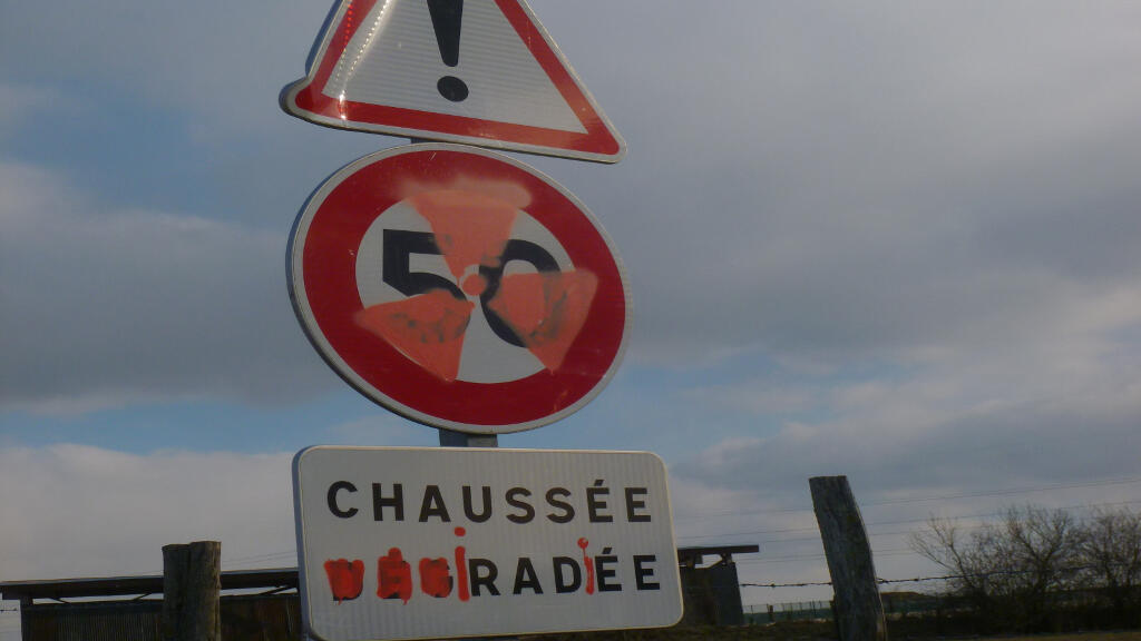"""Opponents tag a """"road removed"""" sign in Bure to read """"road irradiated"""""""