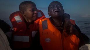 Una niña de 11 años llora al lado de su hermano de 10 años a bordo de un bote de salvamento de una ONG, 28 julio 2016.