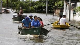 À Asuncion (Paraguay), des personnes se déplacent en bateau à cause des inondations dues au phénomène climatique El Niño. Photo datée du 27 décembre 2015.