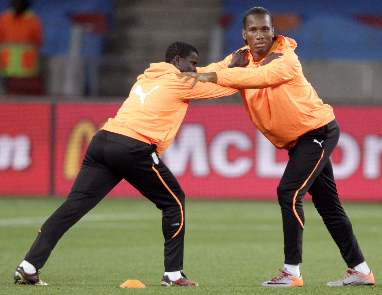 Didier Drogba s'échauffe avec Emmanuel Eboué.