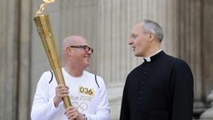 John Elbrow (e) carrega a tocha olímpica nesta quinta-feira, ao lado do reverendo David Ison, da tradicional Catedral de Saint Paul, em Londres.