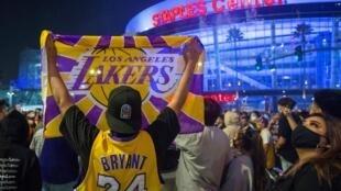 Des fans des Lakers de Los Angeles masqués pour cause de Covid-19 fêtent le sacre NBA de leur équipe et rendent hommage à un Kobe Bryant décédé le 26 janvier 2020.