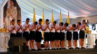 Les jeunes rescapés de la grotte de Tham Luang, honorés avec leur entraîneur et leurs sauveteurs le 6 septembre à Bangkok. Derrière eux, le portrait du roi de Thaïlande.