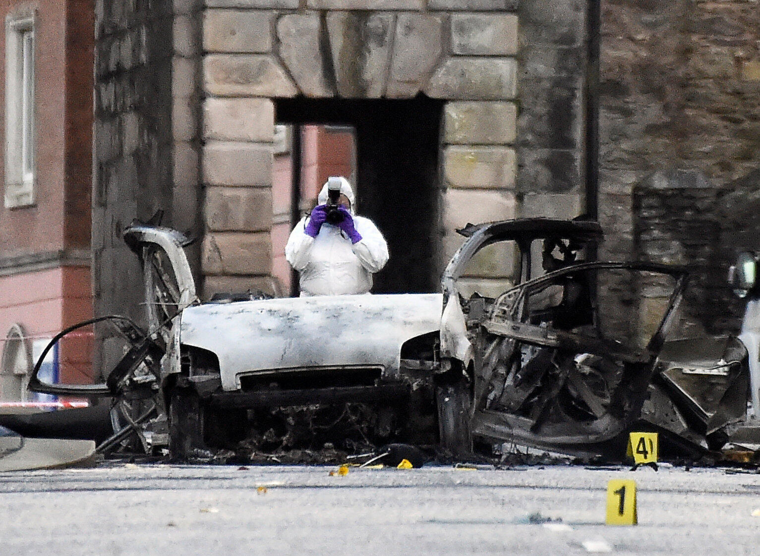 Forensic police inspects car wreck after suspected bomb explosion