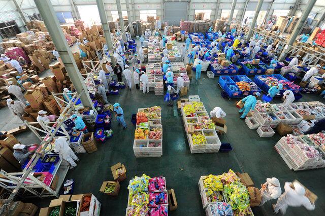 Na China, empregados do site de vendas Alibaba embalam mercadorias compradas em ritmo frenético no Dia do Solteiro.