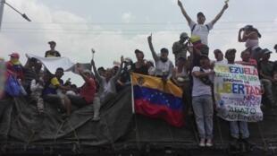 Momento en el que las gandolas atraviesan el puente Francisco Paula Santander con la ayuda humanitaria. Sosteniendo la bandera de Venezuela, Maritza Ramirez. Venezuela, 23 de febrero de 2019.