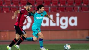 L'attaquant argentin de Barcelone Lionel Messi (R) rivalise avec le défenseur espagnol du Real Mallorca Joan Sastre lors du match de football de la Ligue espagnole entre le RCD Mallorca et le FC Barcelone au stade Visit Mallorca (stade Son Moix).