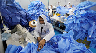 Un homme fabrique du matériel de protection chirurgical dans une usine spécialisée en Égypte, le 15 mars 2020, en pleine crise sanitaire mondiale.