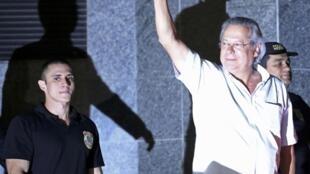 José Dirceu, quien fuera mano derecha del Presidente Luis Ignacio Lula durante su primer gobierno levanta el brazo en saludo a los seguidores que llegaron hasta dependencias policiales para darle su apoyo en momentos en que se entregaba a la justicia.