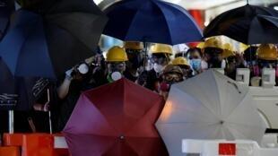 Des manifestants anti-extradition tiennent des parapluies lors d'une marche à Hong Kong, le samedi 3 août 2019.