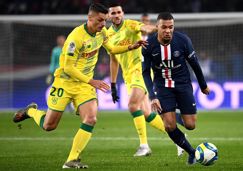 Kylian Mbappé (direita), avançado do PSG, marcou o primeiro tento dos parisienses frente ao Nantes do brasileiro Andrei Girotto (esquerda).