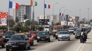 Une avenue à Abidjan avec des drapeaux ivoirien et français annonçant la venue d'Emmanuel macron.