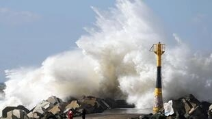 Waves crash near the Luno on a seawall off the beach in Anglet