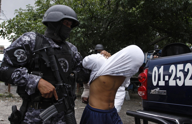 """Un militar detiene a un sospechoso del ataque contra un autobús en el que murieron 14 personas y que las autoridades imputan a la """"Mara 18""""."""