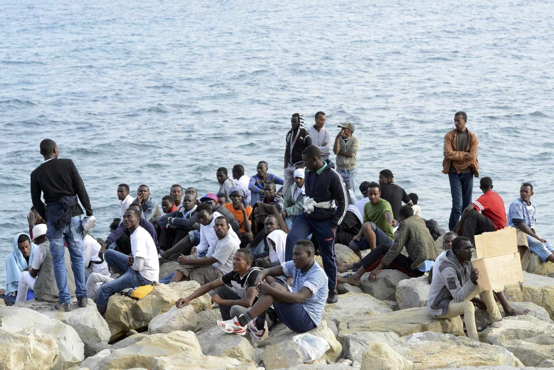 Un groupe de migrants sur les rivages de la Méditerranée à la frontière entre l'Italie et la France.