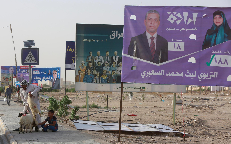 Un homme tient un mouton à vendre à côté des affiches de campagne des candidats avant les élections législatives, à Najaf.