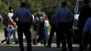 Um grupo de migrantes é escoltado por policiais croatas em Tovarnik, Croácia, em 16 setembro de 2015.