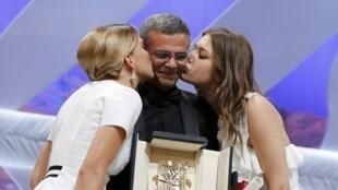Léa Seydoux (G) et Adele Exarchopoulos (D) embrassent le réalisateur Abdellatif Kechiche, après reçu la Palme d'Or pour le film « La Vie d'Adèle », ce dimanche 26 mai à Cannes.