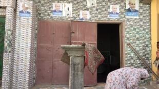 Une femme devant une maison où sont collées les affiches du candidat du pouvoir Mohamed ould Ghazouani.