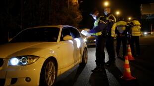 Policiais verificam atestado de motorista que afirma responder a uma das nove exceções que o autorizam sair de casa, apesar do lockdown