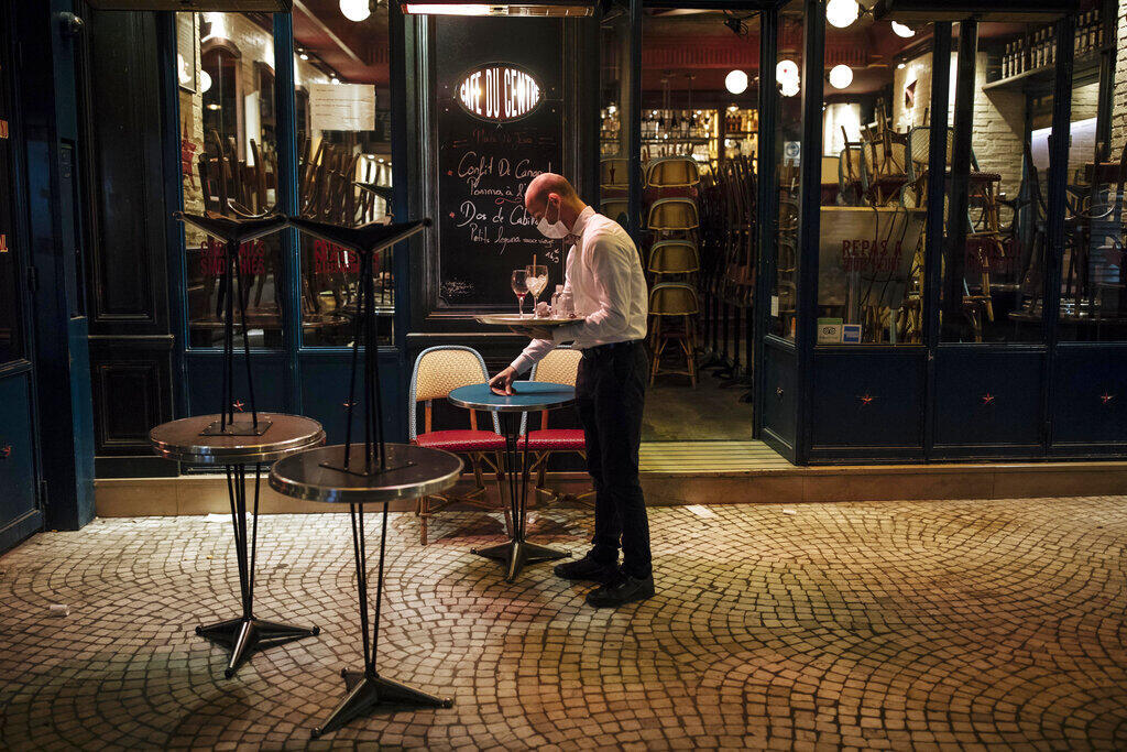 A waiter closes a bar terrace in Paris on Saturday 17 October, 2020. The monthlong curfew came into effect Friday at midnight in Paris and eight other French cities.
