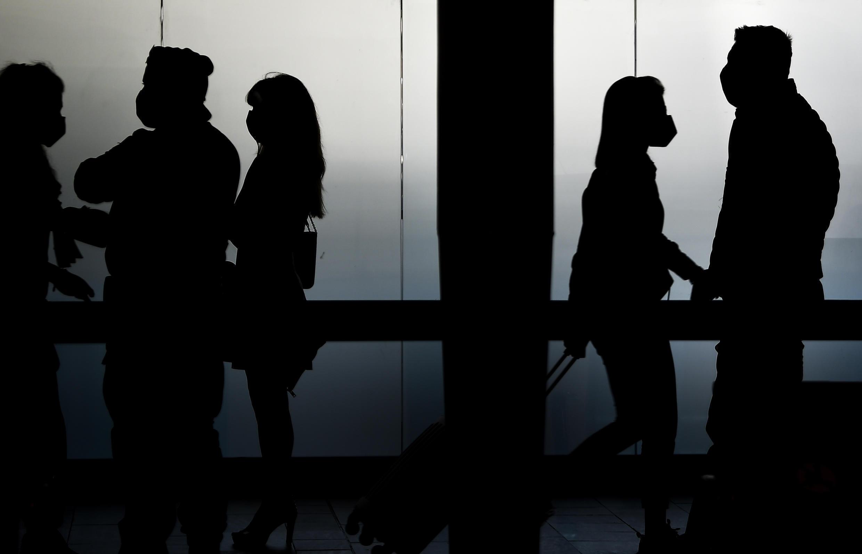 Viajeros con mascarillas en un pasillo del aeropuerto de Fiumicino, en Roma, el 3 de junio de 2020, día de la reapertura de aeropuertos y fronteras