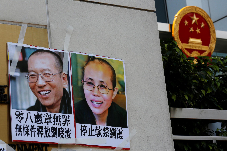 """6月27日,港人在北京最高派出机构""""中港联""""门前挂出刘晓波夫妇画像。"""