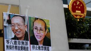 """6月27日,港人在北京最高派出機構""""中港聯""""門前掛出劉曉波夫婦畫像。"""
