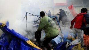 La fumée s'élève des tentes en feu lors du raid des forces de sécurité irakiennes sur la place Tahrir pendant les manifestations anti-gouvernementales en cours à Bagdad, Irak, le 25 janvier 2020.