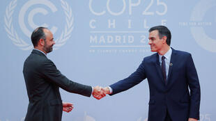 Interim Spanish prime minister Pedro Sanchez (R), and French prime minister, Edouard Philippe (L) shake hands at the opening of the United Nations COP25 summit in Madrid, Spain, 2 December 2019.