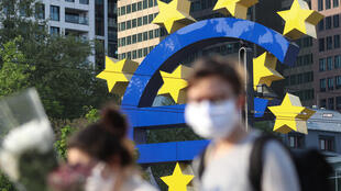 People wear masks outside the Central European bank headquarters in Frankfurt, Germany, April 2020
