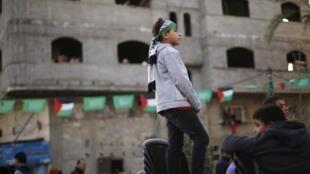 Un jeune palestinien regarde une manifestation dans les rues de Gaza, le seul territoire palestinien qui continue d'être dirigé par le Hamas.