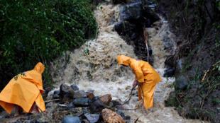 Trabajadores limpian una vía semibloqueada producto del tifón Mangkhut. Luzón, Filipinas.