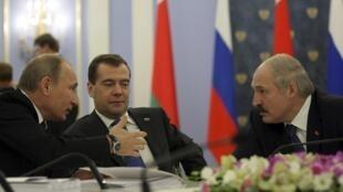 Le Premier ministre et le président russe, Valdimir Poutine et Dmitri Medvedev (gauche et centre) discutent avec le président biélorusse Alexandre Loukachenko, le 25 novembre 2011 à Moscou, en vue d'un accord sur le gaz entre les deux pays.