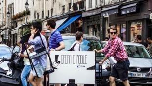 Grupo Opera è Mobile carrega equipamentos pelas ruas de Paris.