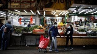 Sur le marché de Tel Aviv, des personnes portent des masques, le 15 mars 2020.