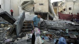 Criança palestina recupera brinquedo nos destroços de uma casa atingida por bombardeios.