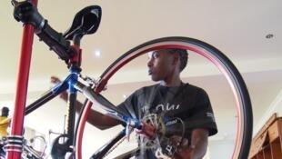 Sandrine Uwayezu prépare les vélos de l'équipe féminine senior pour le championnat africain de cyclisme, à Kigali le 18 février 2018.
