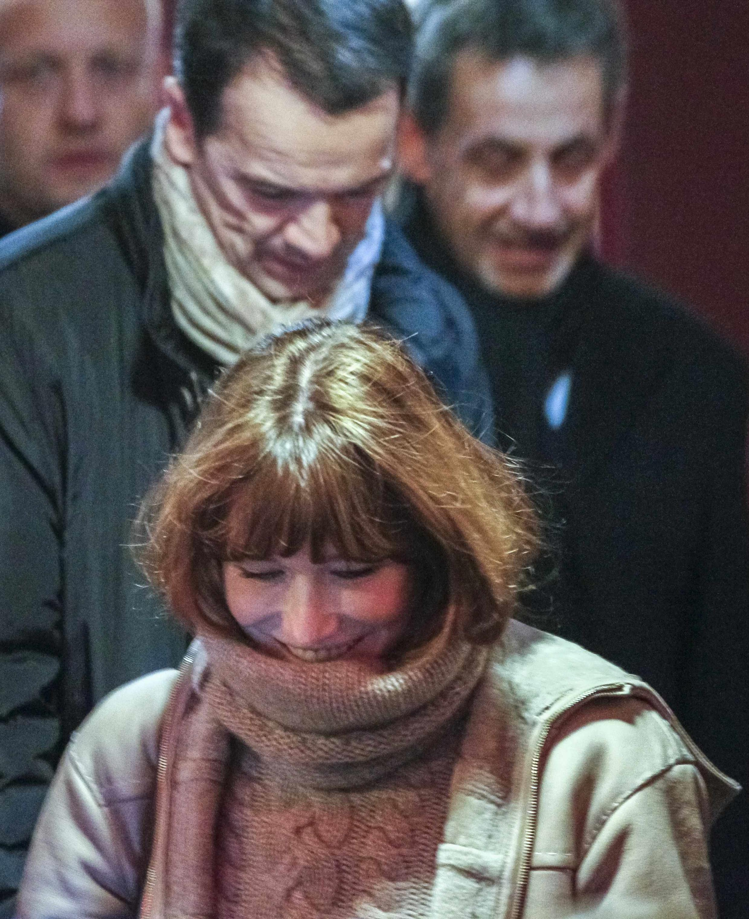 Former first lady Carla Bruni-Sarkozy leaves her concert, followed by her husband, former French President Nicolas Sarkozy.