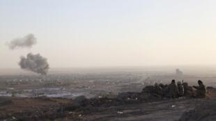 Wapiganaji wa kikurdi wakiangalia mji wa Makhmur katika jimbo la Erbil, kaskazini mwa Iraq, baada ya mashambulizi ya anga ya jeshi la Marekani.