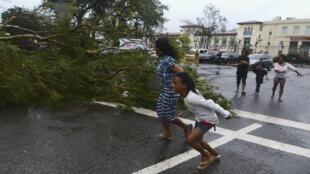 Moradores de Cebu, na região central das Filipinas, correm para se proteger do vento forte que acompanha o tufão Haiyan.