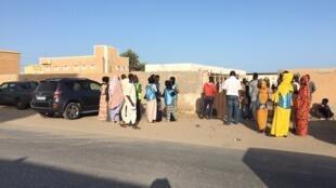 Devant le bureau de vote de Sebkha à Nouakchott, des jeunes font de la sensibilisation pour le compte du candidat le général Ghazouani, Mauritanie, le 22 juin 2019.