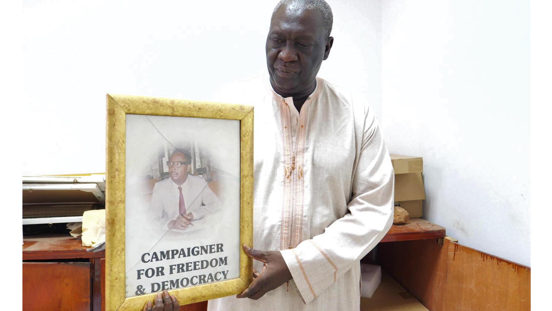 Le journaliste Pap Saine, cofondateur du journal The Point, tenant une photo de son ami Deyda Hydara, dans les locaux du journal The Point (photo prise le 23 juillet 2019).
