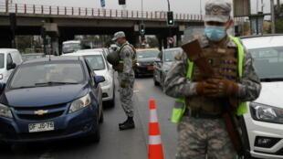 Des soldats chiliens contrôlent des automobilistes après le durcissement des restrictions pour freiner la pandémie de Covid-19, à Santiago, le 18 mars 2021.