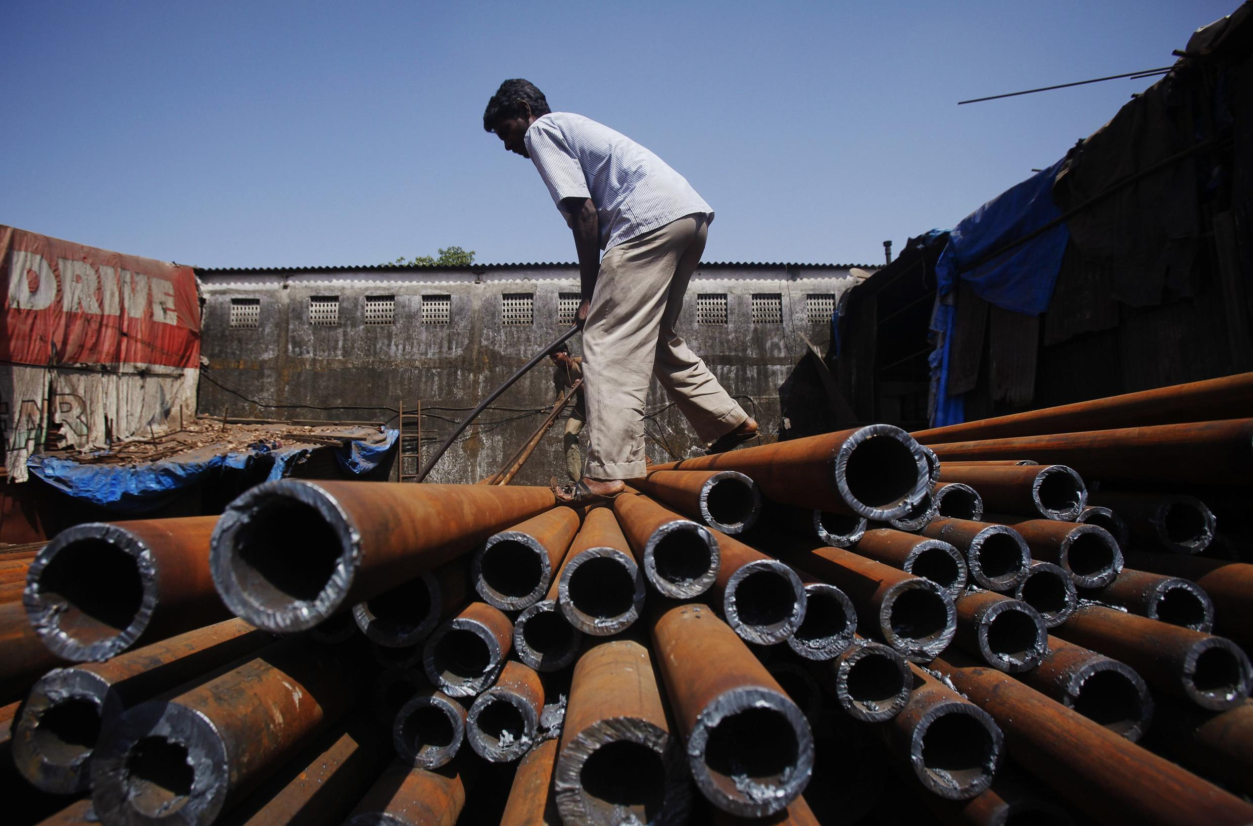 A worker moves iron pipes at a factory in Mumbai. India's economic growth slowed to its weakest annual pace in three years.