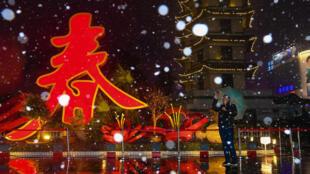 即将到来的中国农历新年前,一名男子在写着《春》字的街景装置旁拍照。2019年1月30日河南郑州