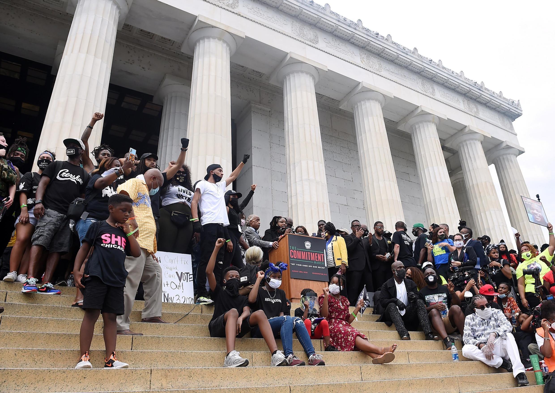 8月28日,抗議者在林肯紀念堂前呼籲族裔平等與司法改革。Des orateurs s'expriment devant le Lincoln mémorial à Washington lors d'un rassemblement contre le racisme, le 28 août à Washington.