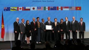 Onze représentants des parties au TPP entourent le Premier ministre néo-zélandais John Key (6e d.), le 4 février 2016 à Auckland.